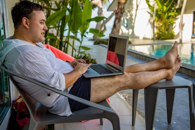 Concetto di lavoro a distanza uomo con laptop seduto a bordo piscina in un paese tropicale