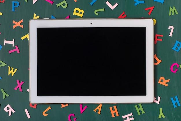 Concetto di lavoro a distanza. in alto sopra la foto vista dall'alto del tablet isolato su una lavagna verde con molte lettere