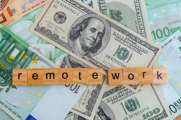 Iscrizione di lavoro a distanza su cubi di legno sulla trama di dollari americani e banconote in euro