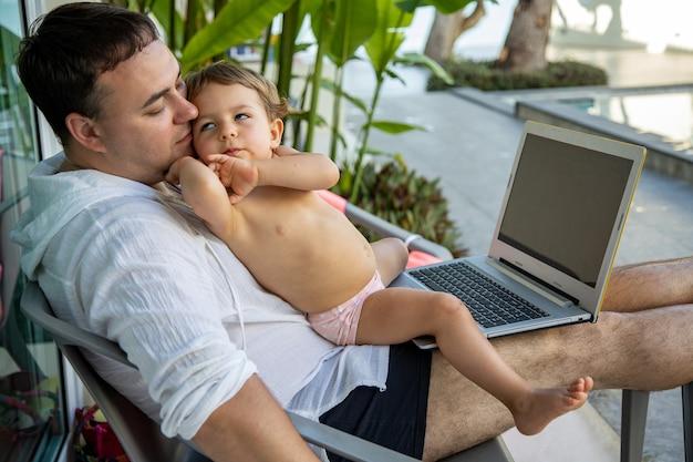 Lavoro a distanza. uomo con un bambino in braccio con un laptop seduto a bordo piscina in un paese tropicale