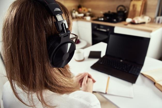 Lavoro a distanza. corsi online, formazione a distanza e concetto di e-learning. la donna in cuffie ascolta il corso audio al computer portatile