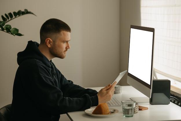 Lavoro a distanza online. un programmatore lavora in remoto utilizzando un computer all-in-one. un collega lavora con un tablet da casa.