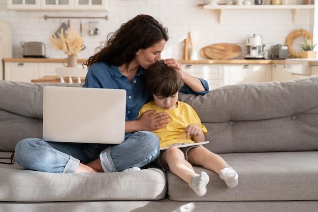 La mamma lavoratrice remota o il libero professionista abbraccia il bambino con il tablet utilizzando il computer portatile per lavorare da casa