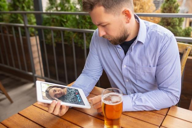 Lavoro a distanza, intrattenimento online durante la quarantena. uomo che guarda lo streaming in bar, ristorante con pc, dispositivi e gadget. concetto di apprendimento a distanza, isolamento, affari, shopping, conferenze.