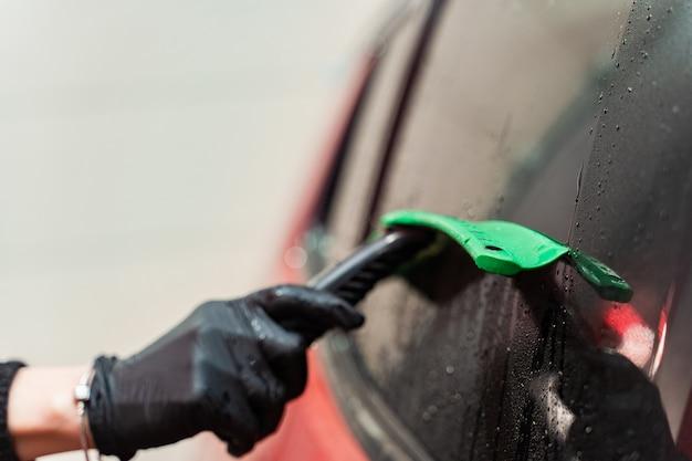 Rimozione dell'acqua residua dal vetro con un raschietto in gomma dopo il lavaggio dell'auto. autolavaggio. complesso self-service. autolavaggio ad alta pressione.