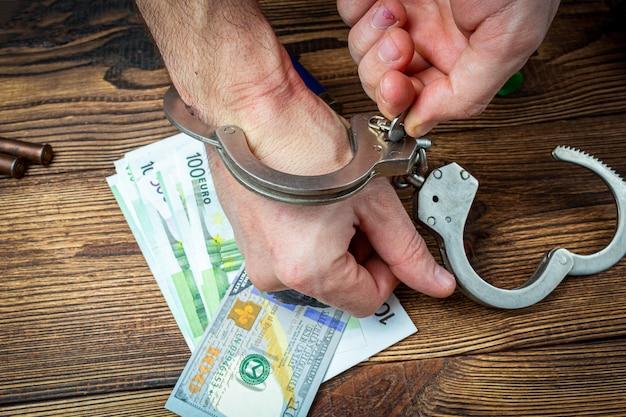 Rimozione delle manette dalle mani sulle banconote di un denaro.