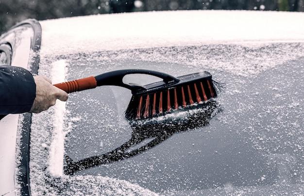 Rimozione della neve dall'auto. pulire il finestrino dell'auto in inverno dalla neve, dalla spazzola invernale e dal raschietto per pulire l'auto dopo una tormenta di neve.