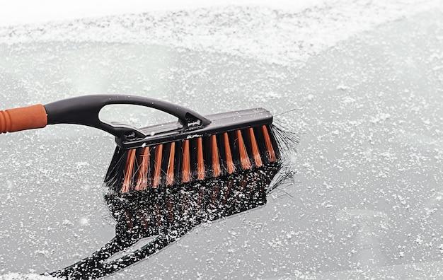 Rimuovere la neve dall'auto. pulire il finestrino dell'auto in inverno dalla neve, dalla spazzola invernale e dal raschietto che pulisce l'auto dopo una tormenta di neve
