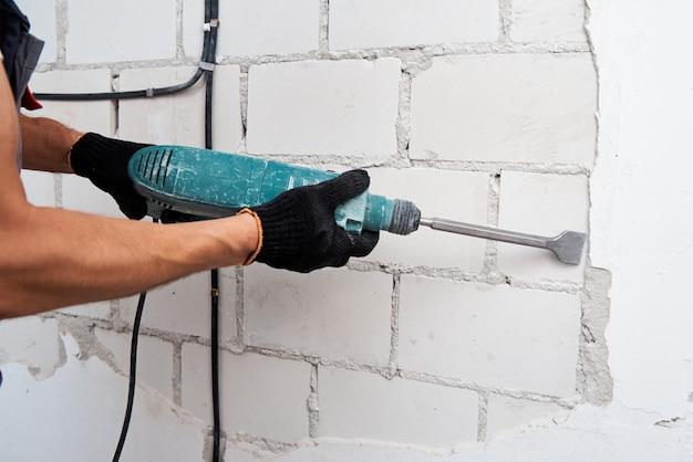 Concetto di ristrutturazione. l'uomo con il martello demolitore rimuove lo stucco dalla parete