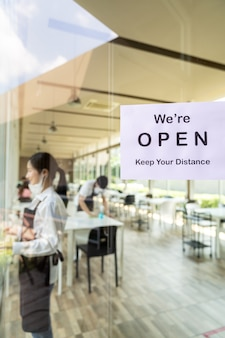 Riapertura della segnaletica del ristorante con distanza sociale per un nuovo ristorante normale con cameriere asiatico e cameriera preparano il ristorante prima dell'apertura. nuovo concetto di stile di vita normale del ristorante.