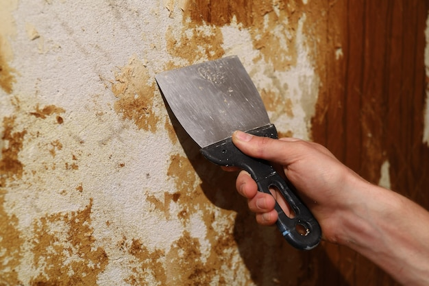 Riparare nell'appartamento strappando la vecchia carta da parati con una spatola