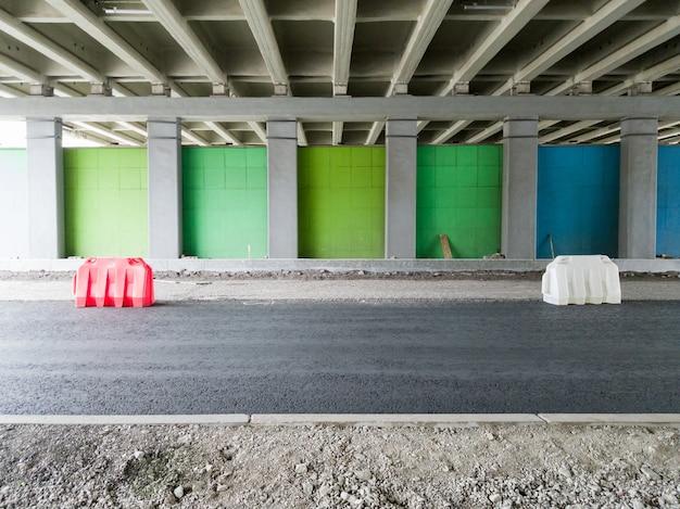 Riparazione di una strada asfaltata per auto recintata con recinzioni in plastica sotto il ponte. ricostruzione della viabilità in città.