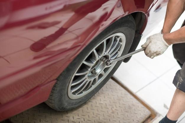Riparare o cambiare pneumatico meccanico del veicolo che avvita la ruota dell'auto alla stazione di servizio di riparazione.