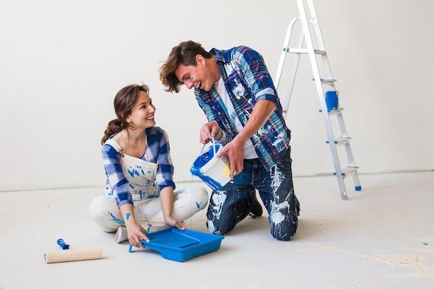 Concetto di riparazione, colore, ristrutturazione e persone: coppia che dipinge il muro, mescola il colore