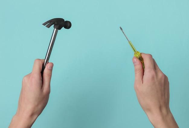 Concetto di riparazione mano femminile tiene un cacciavite e un martello