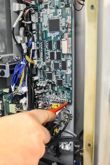 Riparazione scheda elettronica. rimozione della scheda di controllo per sostituzione, controllo e riparazione. svitare i bulloni con un cacciavite. concetto di industria.
