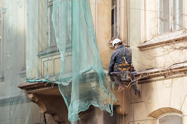 Riparazione della facciata della casa da parte di un uomo su funi di sospensione