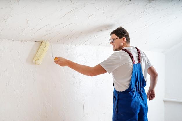 Riparazione, miglioramento domestico e concetto di ristrutturazione. giovane uomo in tuta blu dipinto muro