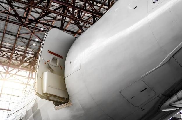 Riparazione e manutenzione della porta di ingresso-uscita dell'aeromobile in coda nell'hangar.