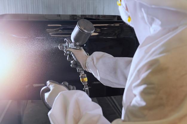 Riparazione e verniciatura di un meccanico.lavoratore che dipinge un'auto