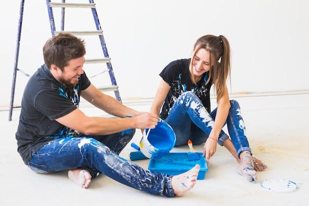 Concetto di riparazione, ristrutturazione e persone - coppia che dipingerà il muro, stanno preparando il colore e i pennelli