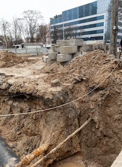 Riparazione di strade e sottoservizi. grande trincea sulla strada con un tubo, il processo di riparazione o sostituzione dei tubi dell'acqua in una grande città. ã â¡costruzione e riparazione di acque sotterranee