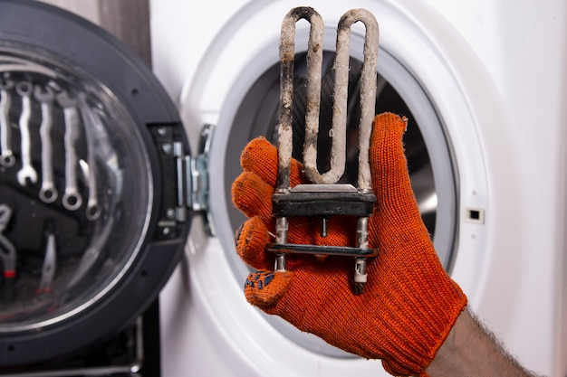 Riparazione di lavatrici. mano di un riparatore con un riscaldatore elettrico turbolento ricoperto da uno strato di acqua dura.