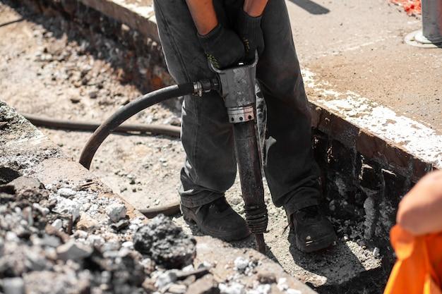 Lavori di riparazione sulla strada della città. i lavoratori professionisti smantellano parte della strada con uno strumento professionale. i lavoratori rimuovono l'asfalto e scavano una buca. esperti tecnici, flusso di lavoro sulla strada della città.