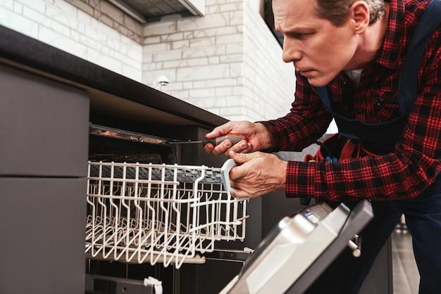 Riparare il tecnico maschio della lavastoviglie seduto vicino alla lavastoviglie