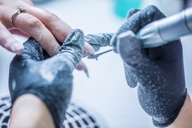 Riparare le vecchie unghie in gel con una smerigliatrice per unghie nel salone dello studio per unghie