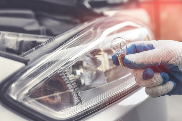 Il riparatore all'autoshop mostra la nuova lampadina dell'auto per la sostituzione, il faro sullo sfondo. luce della lampada