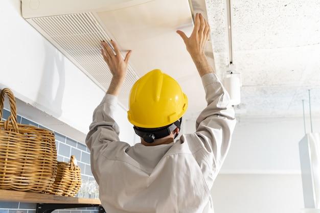 Un riparatore che controlla il condizionatore d'aria