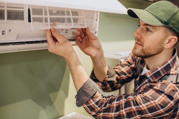 Riparatore che fa servizio di condizionatore d'aria