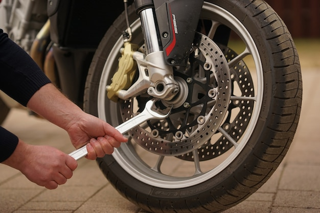 Un riparatore ripara un dettaglio di una motocicletta in un luogo di assistenza