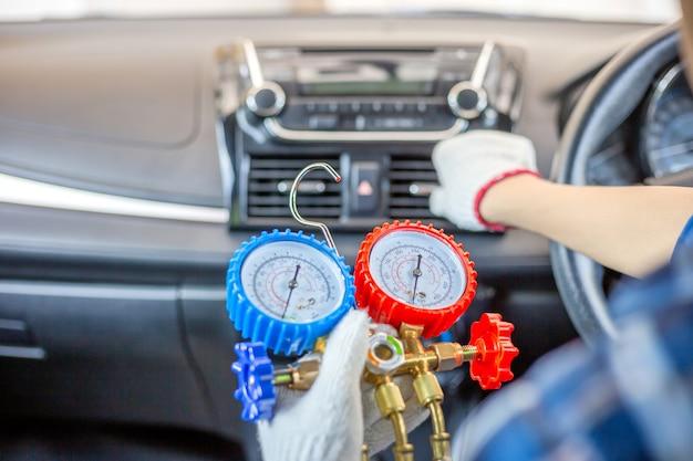 Riparatore che tiene lo strumento di monitoraggio per controllare e riparare il sistema di aria condizionata dell'auto, il tecnico controlla la ricarica del refrigerante del sistema di aria condizionata dell'auto, la riparazione dell'aria condizionata