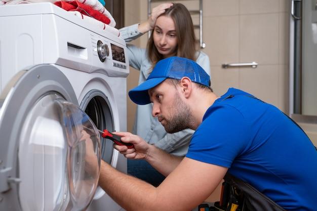 Il riparatore ripara una lavatrice di fronte a una donna che un uomo comunica con il proprietario di una lavatrice