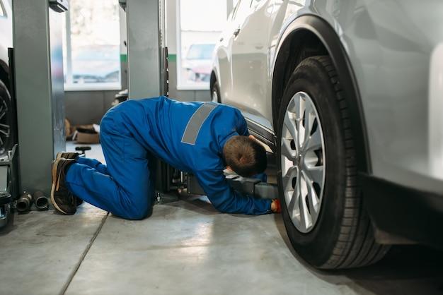 Riparatore in uniforme regola il martinetto di sollevamento in servizio di auto, diagnostica delle sospensioni. servizio automobilistico, manutenzione del veicolo