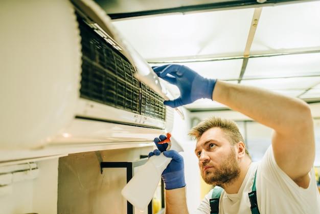 Riparatore in uniforme pulisce il condizionatore d'aria, tuttofare. l'operaio professionista effettua riparazioni in casa, servizio di riparazione domestica
