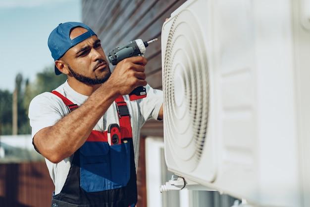 Riparatore in uniforme che installa l'unità esterna del condizionatore d'aria