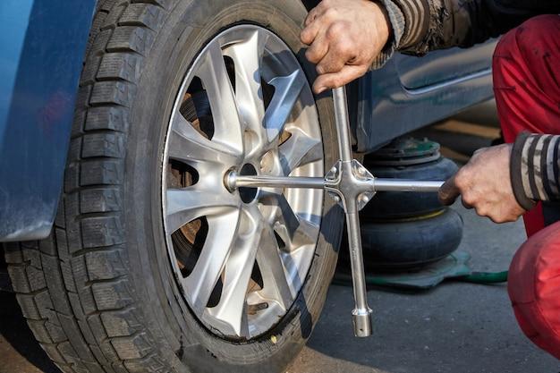 Il riparatore svita la ruota per la sostituzione con una chiave per ruote