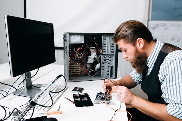 Riparatore di saldatura del circuito del computer in officina. ingegnere barbuto che fissa il componente elettronico. riparazione, sviluppo, concetto di tecnologia