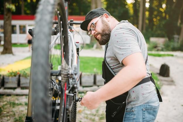 Il riparatore lavora con la ruota della bici, l'officina del ciclo all'aperto. barbuto meccanico di biciclette in grembiule