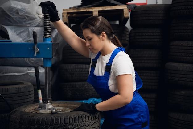 La riparatrice in tuta lavora con una pressa e ruote