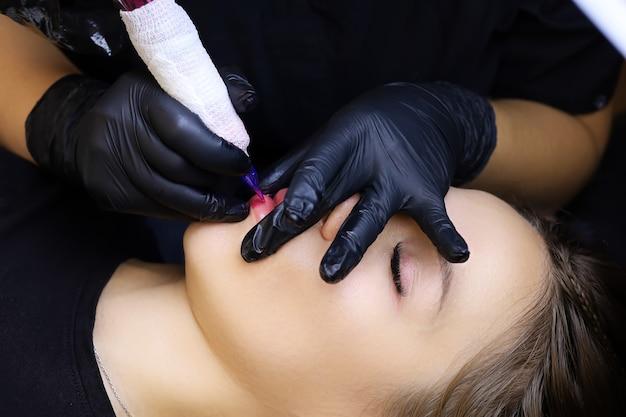 Applicazione ripetuta del pigmento con una macchinetta per tatuaggi sulle labbra della modella
