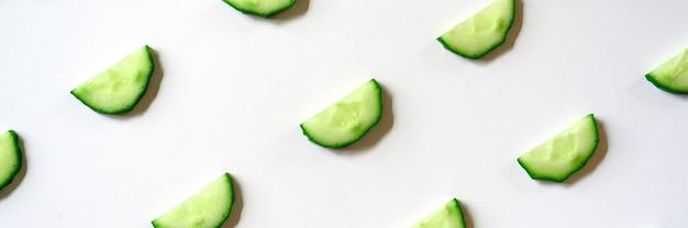 Schema ripetuto di semicerchi affettati di cetrioli vegetali crudi freschi per insalata isolato su uno sfondo bianco piatto, vista dall'alto. striscione