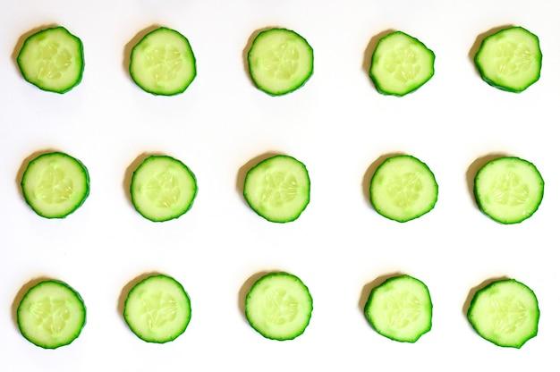 Schema ripetuto di semicerchi affettati di cetrioli di verdure crude fresche per insalata isolato su uno sfondo bianco piatto, vista dall'alto