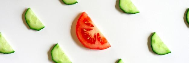 Schema ripetuto di semicerchi affettati di cetrioli di verdure crude fresche per insalata e una fetta di pomodoro al centro isolato su uno sfondo bianco piatto, vista dall'alto. striscione