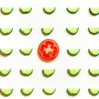 Schema ripetuto di semicerchi affettati di cetrioli di verdure crude fresche per insalata e una fetta di pomodoro al centro isolato su uno sfondo bianco piatto, vista dall'alto. quadrato