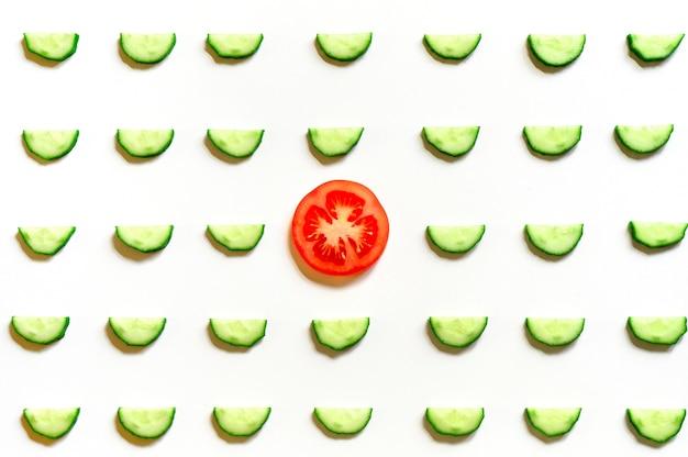 Schema ripetuto di semicerchi affettati di cetrioli di verdure crude fresche per insalata e una fetta di pomodoro al centro isolato su uno sfondo bianco piatto, vista dall'alto