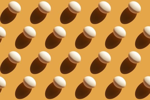 Ripetendo le uova bianche con un'ombra dura su uno sfondo giallo beige, sfondo di pasqua in stile pop art